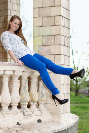 Smiling young blonde in blue pants sitting on ancient handrail photo