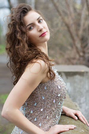 Beautiful young brunette with long curly hair wearing luxury grey dress