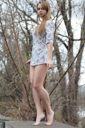 leggy: Barefooted pretty blonde wearing white shirt posing like a statue Stock Photo
