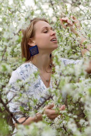 Beautiful young blond woman touching the branch of flowering tree photo