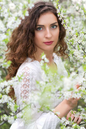 Portrait of young seductive brunette posing in blooming garden photo