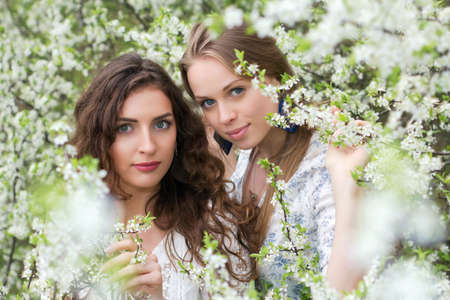 Two nice caucasian ladies posing in blooming garden photo
