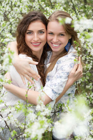 Young caucasian women smiling and hugging in blooming garden photo