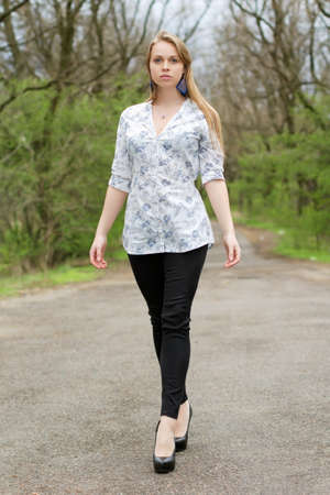 model nice: Thoughtful blonde in white blouse and black pants walking on a footpath