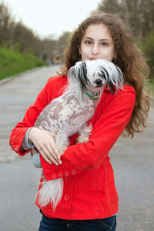 Young caucasian girl in red jacket holding little dog photo