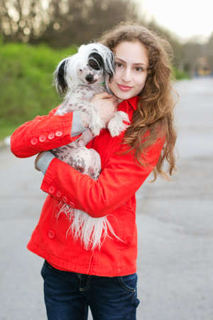 Young curly brunette in red jacket hugging little dog photo