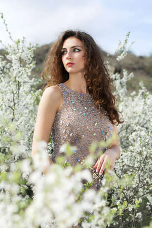Attractive curly brunette wearing grey dress posing in blooming garden photo