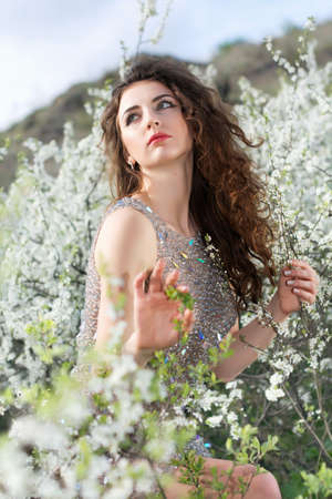 Beautiful curly caucasian lady wearing grey dress posing in blooming garden photo