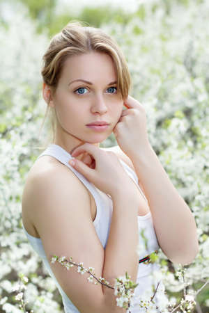 Portrait  of beautiful young blond woman in blooming garden photo