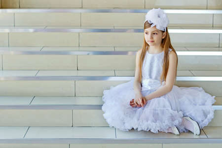Pretty little girl in white dress sitting on the steps photo