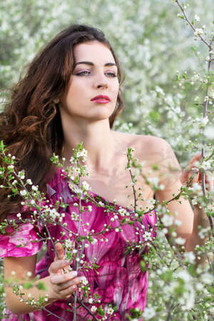 Young thoughtful brunette touching branches of flowering tree Stock Photo