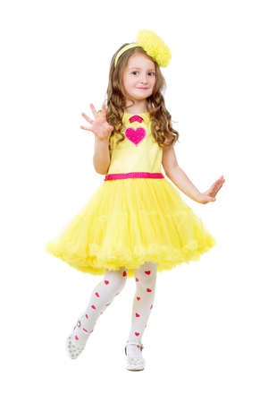 Funny little girl wearing nice yellow dress. Isolated on white photo