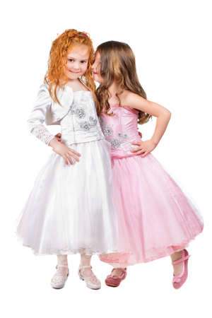 Two little girls in nice dresses whispering. Isolated on white  photo