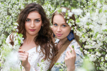 Two pretty caucasian women posing in blooming garden photo