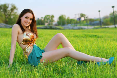 Alluring young woman sitting on the grass and showing her nice long legs