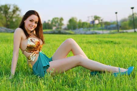 Seductora mujer joven se sienta en la hierba y mostrando sus piernas largas agradables Foto de archivo