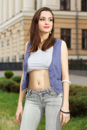 tight jeans: Beautiful smiling lady in short white top posing outdoors
