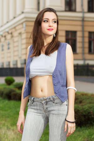 jeans apretados: Bella dama sonriente en la tapa blanca corta posando al aire libre