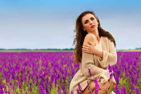 Pretty thoughtful brunette sitting in a flowering field  photo
