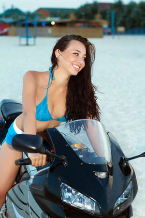 Pretty smiling brunette posing on the black motorbike  photo