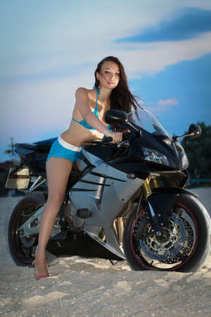 Attractive caucasian woman posing on the bike at sunset  photo