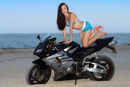 Sexy woman in blue beachwear posing on the black bike photo