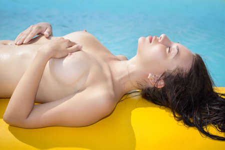 Young caucasian nude woman sunbathing near the water Stock Photo