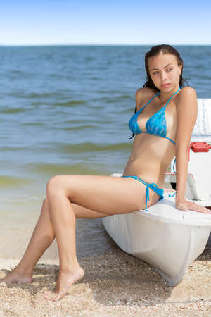Young thoughtful lady in swimsuit posing on the catamaran  photo