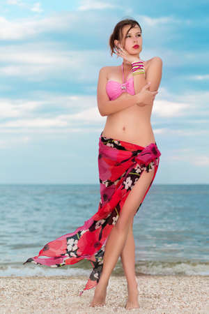flowered: Beautiful young lady in pink bra and flowered pareo posing on the beach  Stock Photo