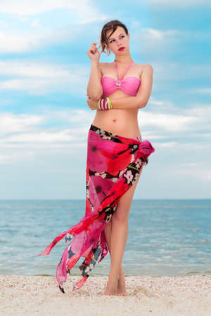 Pretty woman in flowered pareo posing on the beach  photo