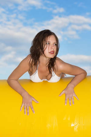 Pretty young woman posing on a background of blue sky with clouds  photo