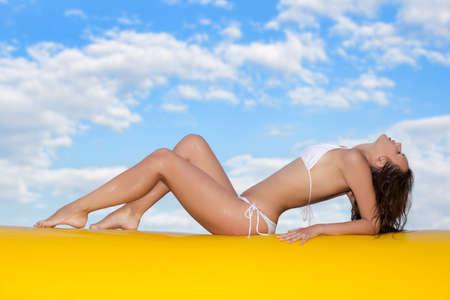 Sexy slim woman sunbathing on the edge of a yellow pool  photo