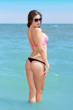 bikini sexy: Young sexy lady wearing beachwear and black sunglasses posing in the sea