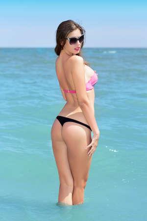 bikini bottom: Young sexy lady wearing beachwear and black sunglasses posing in the sea