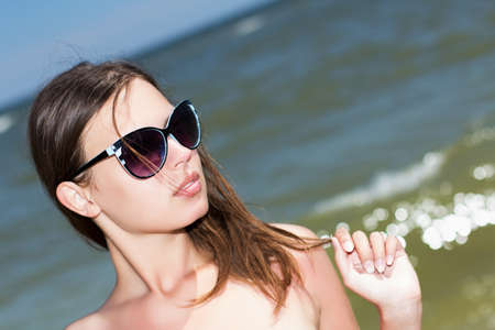 Portrait of pretty woman in sunglasses posing on the beach