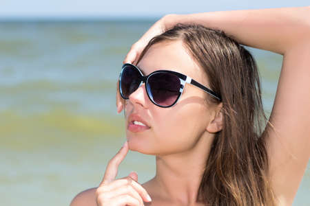 Portrait of sexy woman wearing black sunglasses posing on the beach
