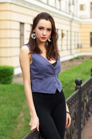 Beautiful young lady posing near the metallic fence photo