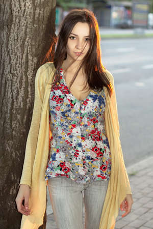 the carriageway: Young thoughtful lady in flowered blouse posing near the carriageway