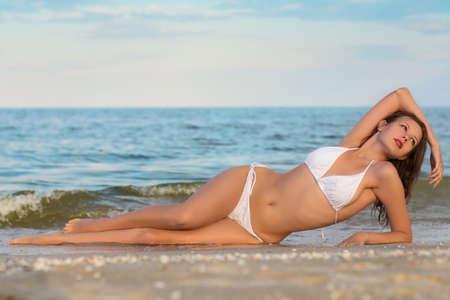 Sexy young woman in white bikini posing on the beach