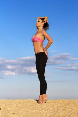 Pretty slim lady in tight black leggings posing on the beach  Stock Photo