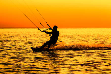 Silhouette of a kitesurfer sailing in the sea at sunset photo