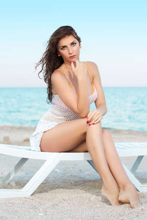 Pretty woman sitting on the beach bed   photo