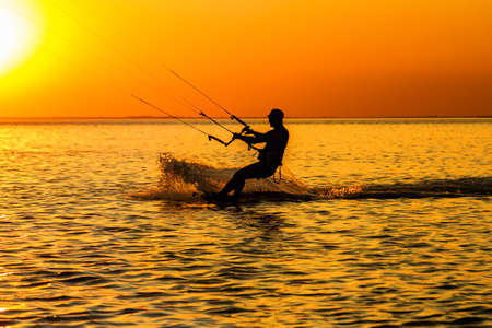 Silhouette of a kitesurfer sailing in the gulf at sunset  photo