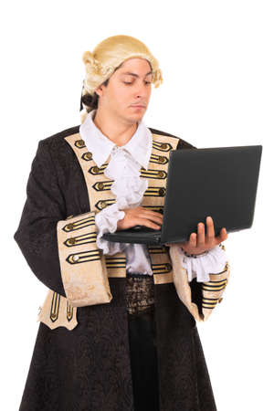 Funny young man wearing medieval costume and posing with a laptop. Isolated on white  photo