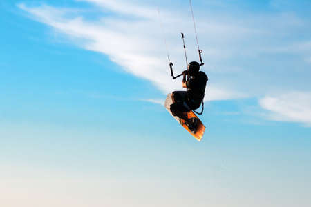 Silhouette of a kitesurfer flying in the blue sky Stock Photo