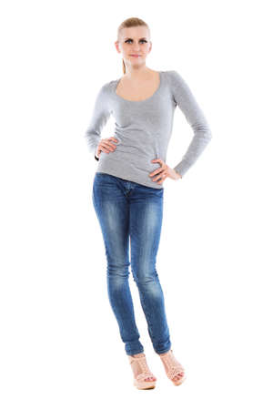 Pretty young blonde posing in blue jeans and grey blouse. Isolated on white  photo