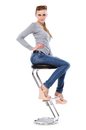 Pretty blond woman in casual clothes posing at the bar chair. Isolated on white  photo