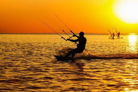 Silhouettes of a windsurfers sailing in the sea at sunset