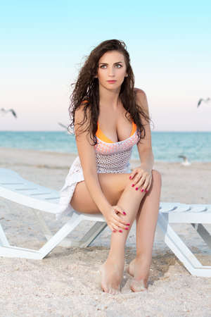 bosom: Young sexy brunette posing on the beach bed