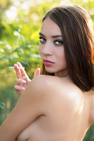Portrait of attractive young brunette posing with cigarette photo